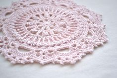 This beautiful crochet doily is a delicate pastel pink colour and has a raised pattern which is a modern variation of the traditional doily. It would make a lovely gift or look delightful in your own home.