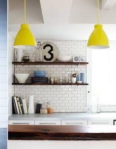 subway tile, open wood shelves, neon yellow pendant lights. love.