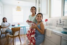 Stock Photo : Smiling girls making jam with berries in kitchen