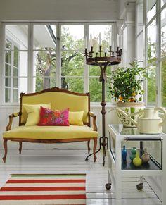 Verandan rymmer en liten soffa och rullbord, båda köpta på loppis. Matta från Kasthall och en golvlj...