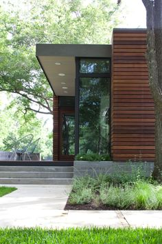 In a family's pint-size lake retreat in Austin, Texas, ipe siding and decking meet concrete floors and steeland-glass windows. Stained cyprus was used for the ceiling and soffit. The custom barn-style sliding door conceals the family's collection of giant inner tubes and other boating equipment.