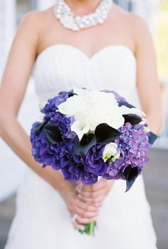 Purple hydrangeas, purple lisianthus, aubergine calla lilies accented by white Polar Star roses, mini calla lilies & freesia