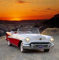 1955 Oldsmobile Super 88 Red And White Convertible 3/4 Front View On Gravel Sunset Background Orange Sky