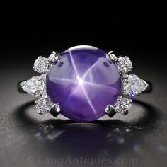 A gorgeous high-domed lavender-blue star sapphire, weighing 11 carats and displaying a distinct, well defined six-pointed star (or asterism), is elegantly presented in platinum between a pair of diamond sprays composed of a pear shape diamond flanked by r Colored Engagement Rings, Buying An Engagement Ring, Bling Bling, Jewelry Rings, Fine Jewelry, Jewlery, Diamond Rings, Gemstone Rings, Blue Star Sapphire