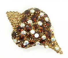 The unusual design pin features amber rhinestones accented by iridescent stone accents. Set in gold tone frame. Signed for Schiaparelli on the back as pictured. Elsa Schiaparelli was a famed fashion designer in Paris in the 1930s.   eBay!