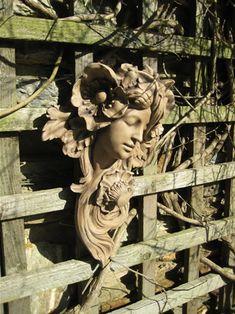 Art Nouveau sculpture on a a garden wall.
