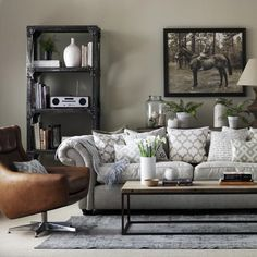 Mix classic and contemporary to create a living room with its own unique sense of style. Go grand with a large sofa as the focus of the room, then offset the traditional with a modern statement chair, tough metal shelving and a raw wood table for contrast