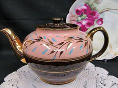 OFFERING THIS FANTASTIC TEAPOT , MADE BY SADLER THIS IS A BEAUTY IT IS A VINTAGE PIECE MADE IN THE EARLY 1930S STUNNING DESIGN AND COLORS , NICE BROWN WITH A BAND OF PINK AND PAINTED AND TRIMMED AND DETAILED IN GOLD AS WELL WITH GOLD RINGS AND HANDLE AND SPOUT DID NOT SEE ANY CHIPS OR