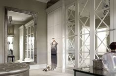 Elegant closet design with gray grasscloth wallpapered walls highlighting a Restoration Hardware Venetian Beaded Mirror alongside custom light gray closets beside x mullion mirrored closet doors across from a round gray tufted ottoman.