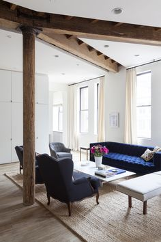 A navy velvet sofa and a rectangular white coffee table . . I like the look with the rug, and like the idea of chairs and/or a chaise.