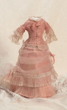 Theriault's Antique Doll Auctions - French Silk and Sheer Muslin Costume - The rose silk three-piece gown features a fitted jacket with double-tiered ruffles on sleeves and around the hemline; matching skirt with flat front and bustle back with demi-train; the skirt overlaid with sheer organdy arranged in folds with double rows of pleats and demi-train. French,circa 1870.