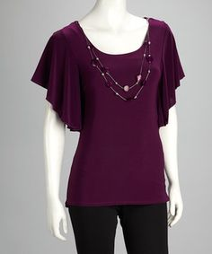 No need to fret about accessorizing in this striking blouse. The cape-sleeve silhouette and accenting necklace provide ample sophistication to any ensemble.
