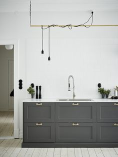 Worktop in Carrara marble - lighting twisted on pipes is so clever - love the huge grey cabinet drawers and gold accents