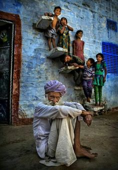 INDIA: Elder overlooked by children on stairsteps of blpue wall.   A beautiful portrait.