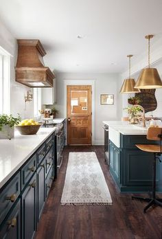 Warm details, like the vent hood, the brass pieces, and the antique doors leading to the music room and laundry room make the space feel finished.