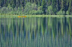 Photograph by Stuart Litoff.  A yellow canoe on Pyramid Lake in Jasper National Park, Alberta, Canada