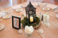 Moss and lantern centerpieces small containers with a touchnof floral to accent