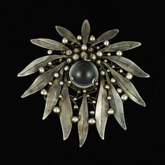 Brooch   Mary Gage.  Long, outward pointing sterling silver leaves decorated with silver beads surround a beautiful clear round rock crystal cabochon. ca. Pre 1950
