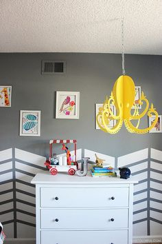 Create a whimsical environment for your kid's bedroom with a fun chevron pattern. We love how this neutral gray wall and accent pattern in Snowbound SW 7004 allow the colorful toys and decor to really stand out. See how to create this look in your kid's room at home.