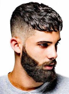 Corte de chico degradado con la parte de arriba más larga y barba.