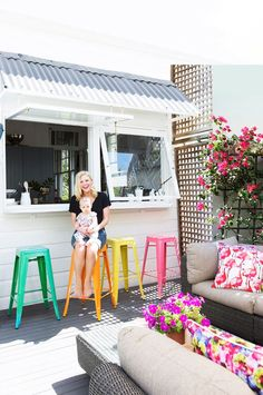 """With servery windows opening out from the kitchen, the deck is a much-used space. The colourful stools are from [Matt Blatt](http://www.mattblatt.com.au/ target=""""_blank"""")."""
