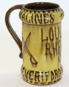 A Dicker slipware mug, with painted script, 'Louvain Rheims, 1914, Never Forget the Huns' in brown slip against a cream ground, 6.5ins