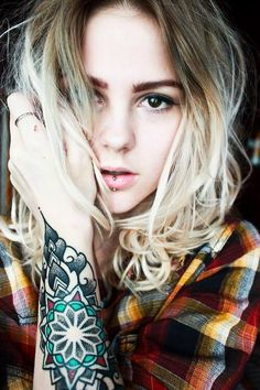Forearm tattoo and lip piercing. Great look. Tattooed photography.