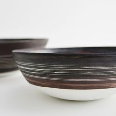 "porcelain bowl. approx 10.5"" wide, 3"" high. wheel thrown. glazed glossy black on the interior, unglazed exterior, matte black/brown with..."