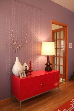 Dining room - Red buffet, lavender walls, white vase, beads hanging behind -- LOVE // Oak Park Apartment // Making It Lovely