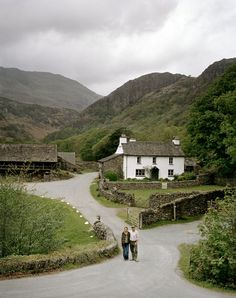 Lovely white cottage nestled between the hills. reminds me of Lake District or Wales
