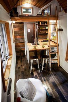 lambris bois massif, sol en parquet foncé, coin cuisine avec buanderie et fauteuil design