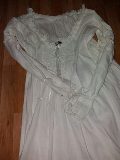 Camia: camisa de señora, bordada a mano con hilo blanco, tablas en las mangas y pechera, escote u puños recorridos con puntillas de ganchillo hechas a mano. Botones antiguos y también forrados. Se trata de una camisa hecha con lino 100% natural