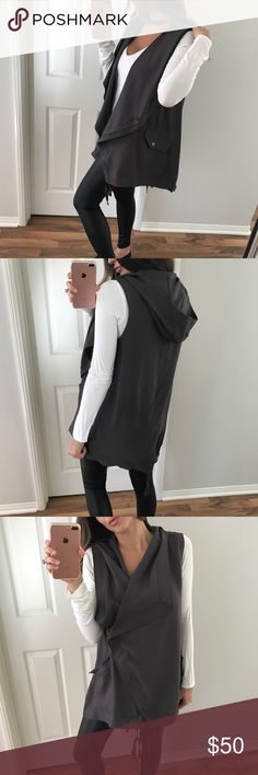 "Dark Grey Jacket Vest This is one of my favorite looks. This vest can be paired in so many ways. Features, a wide collar, attached hood, adjustable bottom ties to make it as fitted as you'd like and a asymmetrical front zipper. Two front button snap pockets. Very well made, quality is amazing. In person the fabric is so beautiful. Looks great with a long sleeve or tank under it.   Modeling • S  Measures • 30"" long 19"" chest  Size Difference • 1"" all over  Fabric • 70% cotton 30% poly Jackets…"
