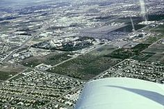 Aerial photo of Disneyland and the surrounding area, including the Disneyland Hotel with its Monorail Station, the Disneyland Heliport, orange groves, Santa Ana Freeway and Melodyland Theater, May 1965