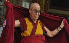 Tibetan spiritual leader Dalai Lama puts on his robe at the Tsuglakhang temple in Dharmsala, India during his 77th birthday celebration on 06 July 2012