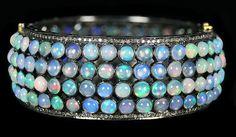 Opal & Diamond Bangle Bracelet, accompanied by 47.95 carats of Opal and 2.50 carats of Diamonds. Set in 14 karat Yellow Gold & Silver.