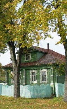 Russian wooden house in the countryside. Baby blue picket fence!