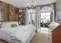 This bedroom screams SHABBY CHIC! Loving the brick wall and large french doors. This home happens to be the Eat Pray Love home too and it's for sale!