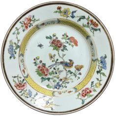 A Chinese export porcelain famille rose plate decorated with a bird. Yongzheng period. Decorated in the famille rose palette, with a yellow cast, a bird on a branche. On the rim, flowers.