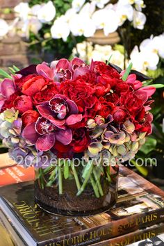 Empty Vase Florist of Los Angeles  Romanticize  Roses, Cymbidium Orchids, Hydrangea, Calla Lilies, Ranunculus and Tulips in a cylinder glass vase with gravel and sand.
