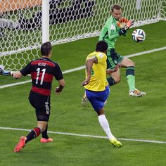 Germany's goalkeeper Manuel Neuer saves a shot by Brazil's Paulinho during the World Cup semifinal soccer match between Brazil and Germany at the Mineirao Stadium in Belo Horizonte, Brazil, Tuesday, July 8, 2014. Left is Brazil's Oscar.(AP Photo/Hassan Ammar)