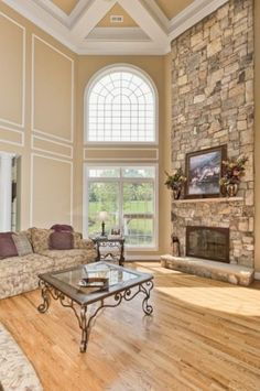 High palladium window above large door with transom window. Sandy-ecru colored wall & ceiling, sofa upholstery, wood floor & colors in rough stone fireplace wall all blend nicely.