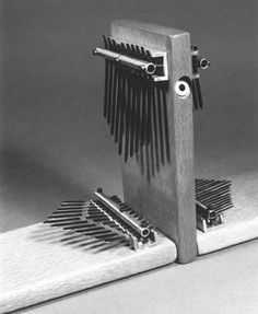 The Koralimba    The koralimba is a double sided electric kalimba with tines arranged under the thumbs and forefingers in a pattern that mimics the notes that the thumbs and forefingers can reach on the strings of the west african harp-lute known as a kora.    The koralimba pictured here is surrounded by two lacewood electrics.