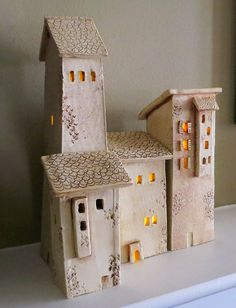 These Four Ceramic Houses are reminiscent of the house found in the hill towns of Tuscany Italy, I visited Sienna and San Gimignano and created these houses from my memory of my visit there. There are four houses they measure in height from 5 1/2 to 11 1/2 and are 2 3/4 wide and 2 3/4 deep except the smaller house which is 2 1/2 wide and 1 3/4 deep.    They were bisque fired then a stain was applied and then fired again. An acrylic matt sealer was applied. Three battery operated lights are…