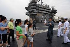 Mass Communication Specialist 2nd Class Peter Burghart, from Colorado Springs, Colo., right, explains flight operations to Republic of Korea locals on the flight deck of the U.S. Navy's forward-deployed aircraft carrier USS George Washington (CVN 73) (U.S. Navy photo by Mass Communication Specialist 3rd Class Eric Scot Brann/Released)