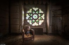 "Well-loved: A dusty toy doll sits in a decaying leather armchair in front of a stained glass window.   The impressive stained glass window of ""Chateau Clochard"". This 15th century castle located in a small French village was an icon for urban explorers. Several pianos were left behind by the former owners who abandoned it over a decade ago. Sadly a fire ravaged the remains of the castle in 2012. Only the outer walls remain."