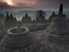 "On this day the sun rose directly behind the active Merapi, ""Fire Mountain,"" highlighting the volcanic smoke which steadily streamed across the horizon from its uppermost region. Facing the mountain in the image is a sacred and latticed stupa of Borobudur Monument's first upper terrace and an endearing statue of Buddha. Thick fog filled the forest and villages below,"