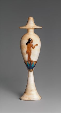 The shape of this perfume bottle imitates that of a ritual vessel used for water libations. Inlaid on its side is a marvel of lapidary skill-a little Amarna princess standing on a blossom of the blue lotus, a species that opens anew each morning with the rising sun