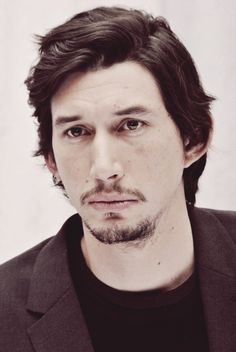Adam Driver with short hair and goatee, black coat and shirt