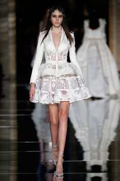 Couture Spring/Summer 2016  White jacket in scuba with cutaway boned panels at the waist, embroidered with lace appliques, paired with a structured cage skirt embroidered with floral guipure appliques